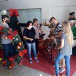 Pessoas ornamentam a porta da Prefeitura de Nova Friburgo com decorações de Natal.
